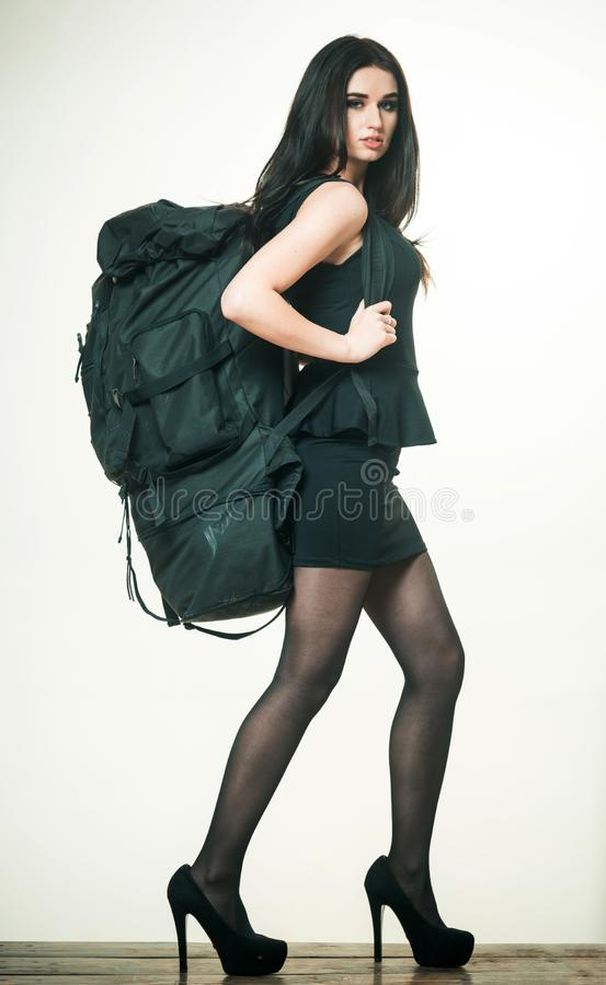 Portrait de femme de brune dans peu de robe noire s'inquiétant le grand sac à dos lourd Joli modèle marchant sur des talons hauts photos stock