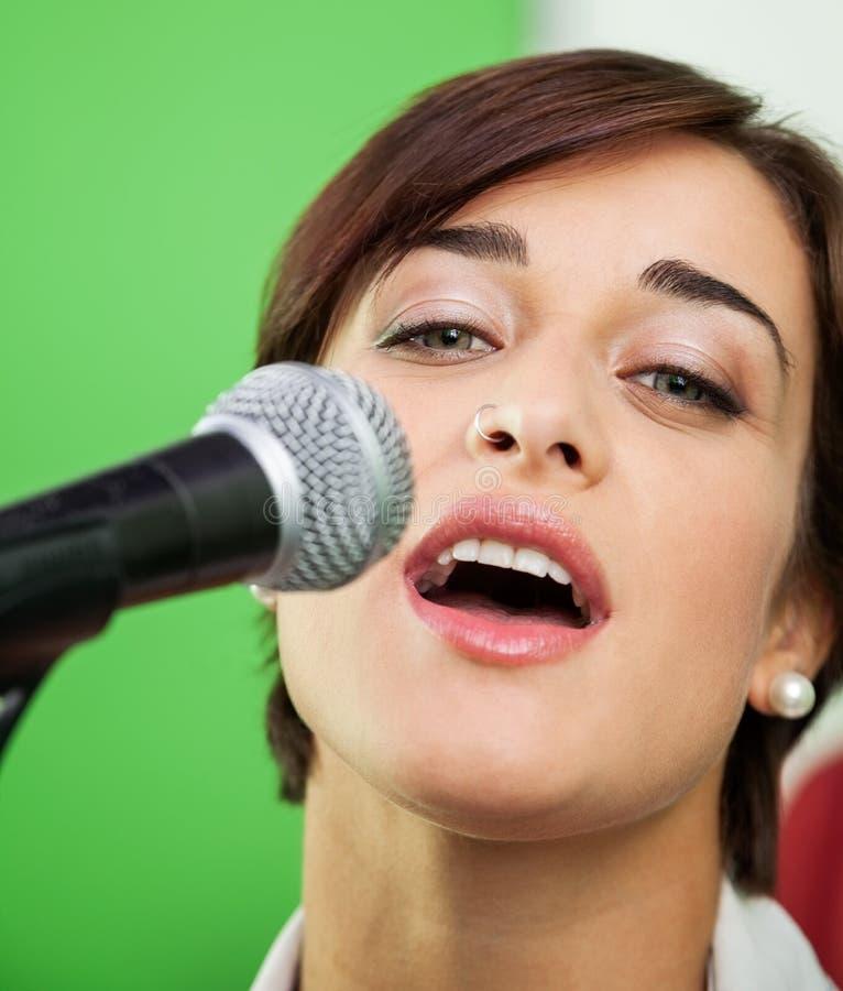 Portrait de femme chantant dans le studio d'enregistrement photos stock