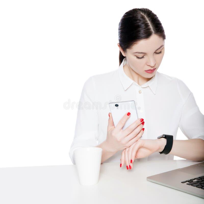 Portrait de femme d'affaires attirante de brune dans la séance blanche de chemise, tenant le mobile de smartphone et regardant l' photographie stock libre de droits