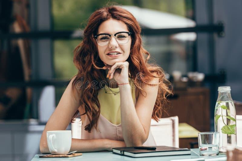 portrait de femme d'affaires attirante dans des lunettes se reposant à la table avec la tasse du café et du carnet photos libres de droits