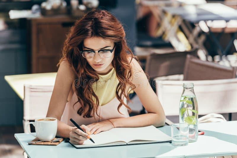 portrait de femme d'affaires dans des lunettes faisant des notes dans le carnet à la table image stock