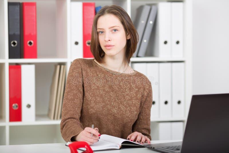 Portrait de femme d'affaires dans le bureau utilisant l'ordinateur portable et les notes de fabrication images stock