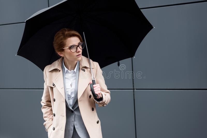 portrait de femme d'affaires dans le manteau élégant avec le parapluie photos stock