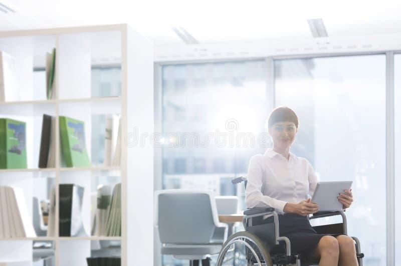 Portrait de femme d'affaires handicapée de sourire avec le comprimé numérique se reposant sur le fauteuil roulant au bureau image libre de droits