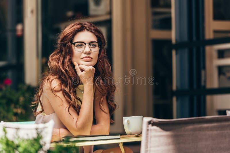 portrait de femme d'affaires songeuse dans des lunettes à la table avec la tasse du café et du carnet photos stock