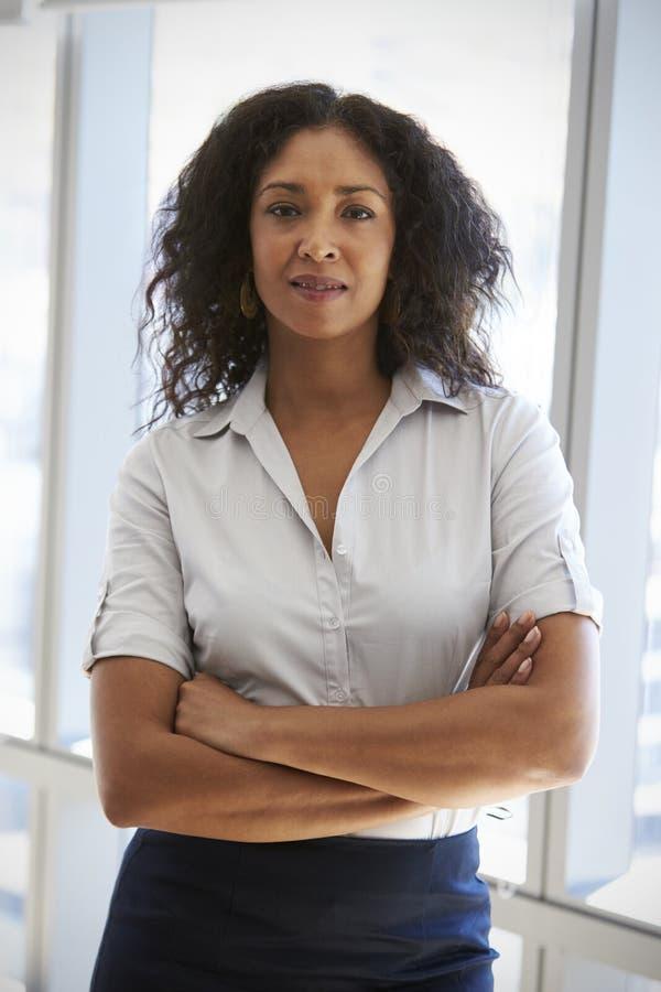 Portrait de femme d'affaires Standing By Window dans le bureau photos stock