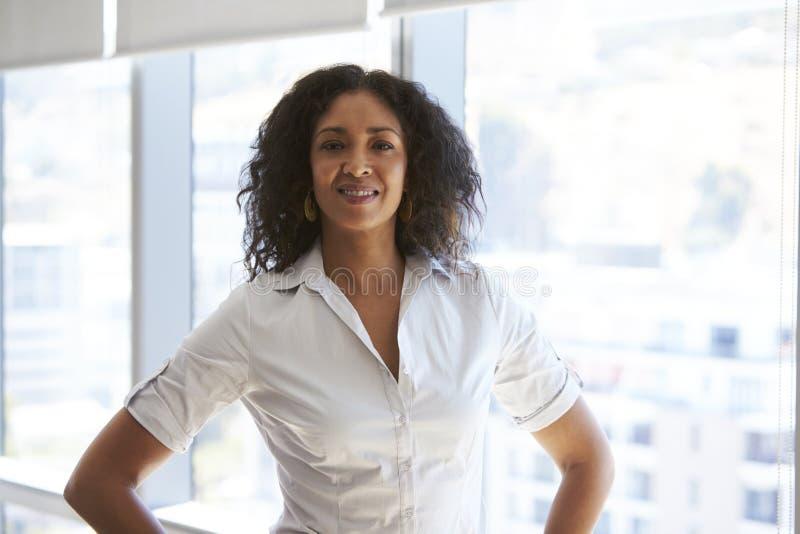 Portrait de femme d'affaires Standing By Window dans le bureau photographie stock libre de droits