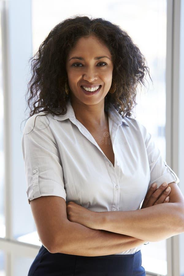 Portrait de femme d'affaires Standing By Window dans le bureau photo stock