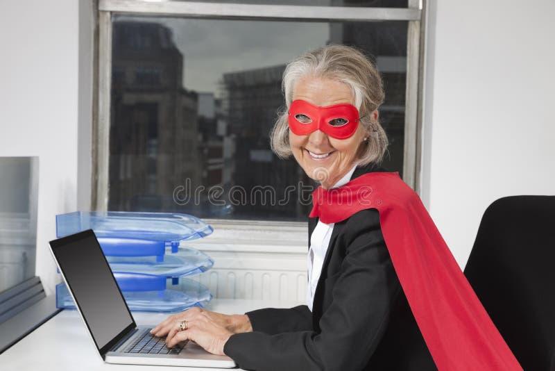 Portrait de femme d'affaires supérieure dans le costume de super héros utilisant l'ordinateur portable au bureau photo stock