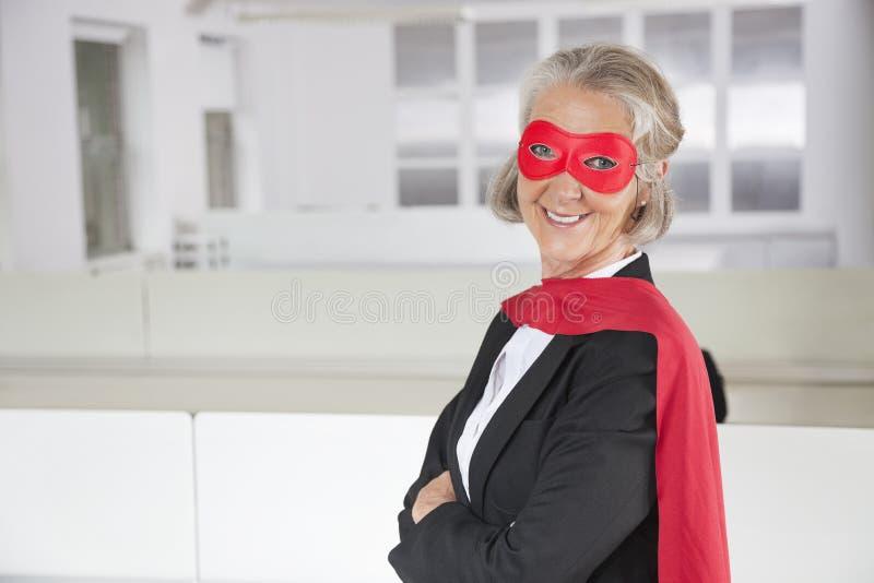 Portrait de femme d'affaires supérieure de sourire dans le costume de super héros dans le bureau photo libre de droits