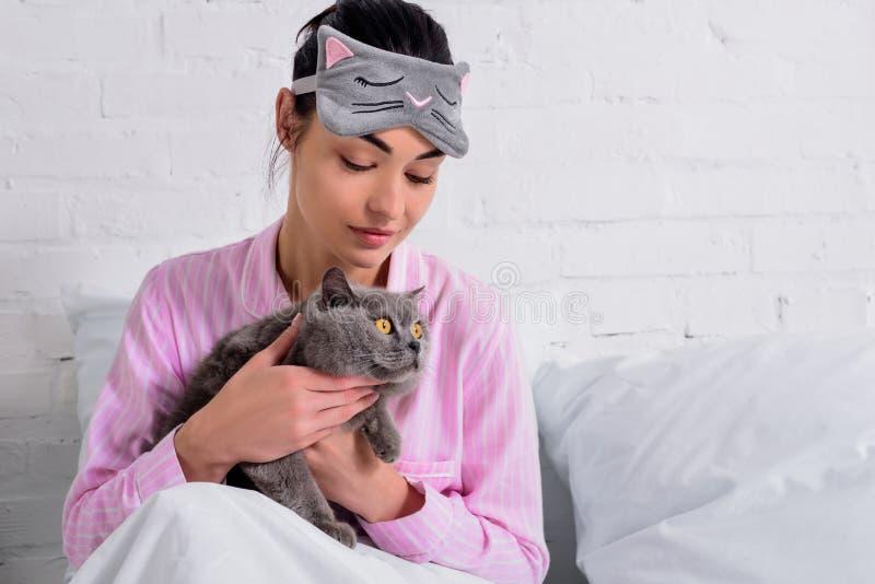 portrait de femme dans des pyjamas et de masque de sommeil avec le chat de shorthair de la Grande-Bretagne se reposant dans le li images libres de droits