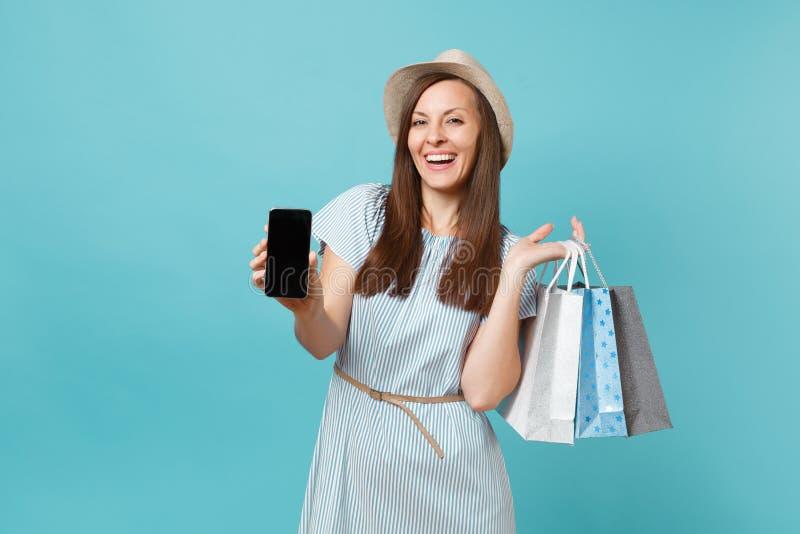 Portrait de femme dans la robe d'été, chapeau de paille tenant des sacs de paquets avec les achats après l'achat, téléphone porta photo stock