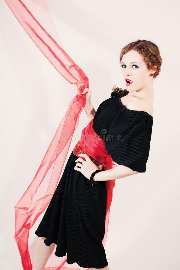 Portrait de femme dans la robe noire avec la ceinture rouge images stock