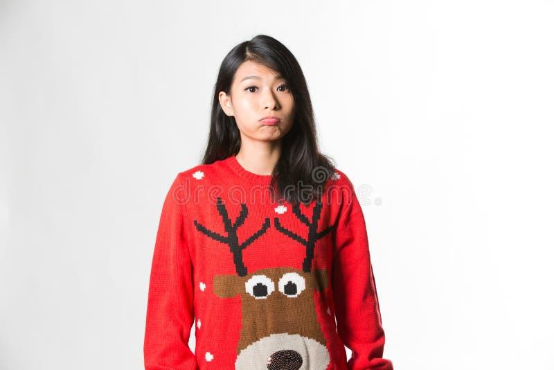 Portrait de femme dans le chandail de Noël se tenant faisant le visage drôle au-dessus du fond gris photographie stock