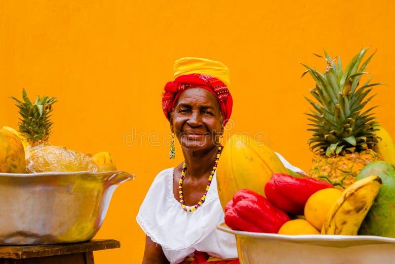 Portrait de femme dans le costume traditionnel avec un panier des fruits, à un arrière-plan jaune de Carthagène de Indias images stock