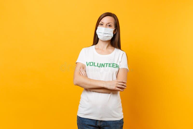 Portrait de femme dans le masque protecteur stérile blanc, T-shirt avec le volontaire écrit de titre de vert d'inscription d'isol photos libres de droits
