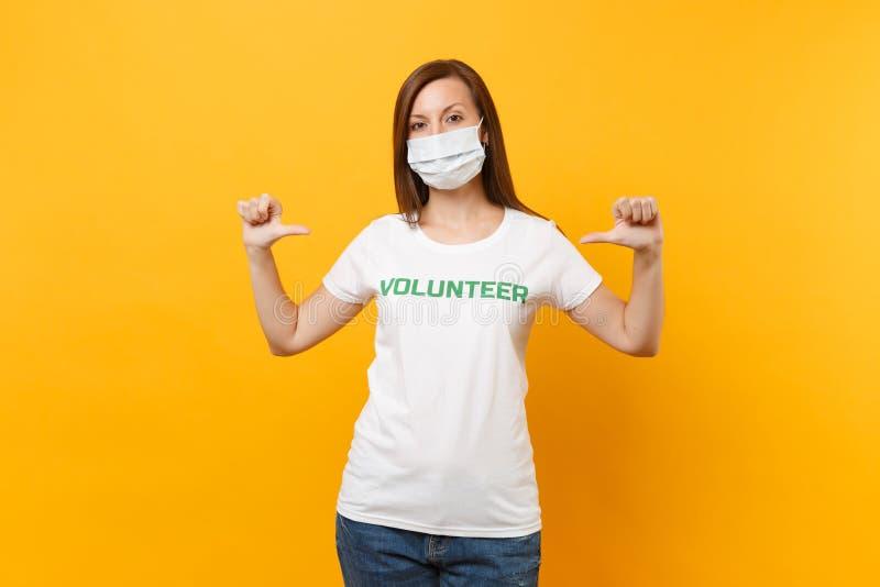 Portrait de femme dans le masque protecteur stérile blanc, T-shirt avec le volontaire écrit de titre de vert d'inscription d'isol images stock
