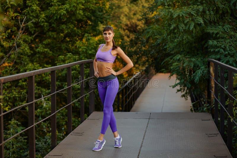 Portrait de femme dans le sportwear faisant la forme physique de séance d'entraînement s'étendant sur le fond urbain de ville Cor photo stock