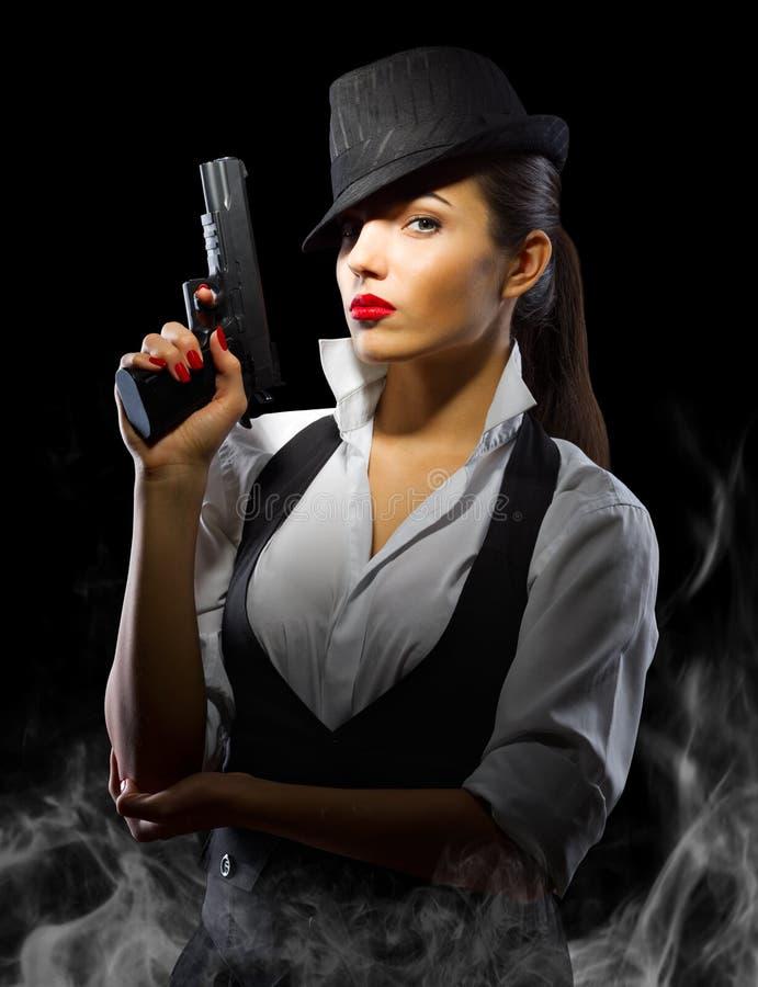 Portrait de femme dans le style viril avec l'arme à feu et la fumée images libres de droits