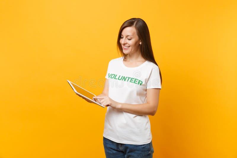 Portrait de femme dans le T-shirt blanc avec le volontaire écrit de titre de vert d'inscription utilisant l'ordinateur de PC de c photographie stock