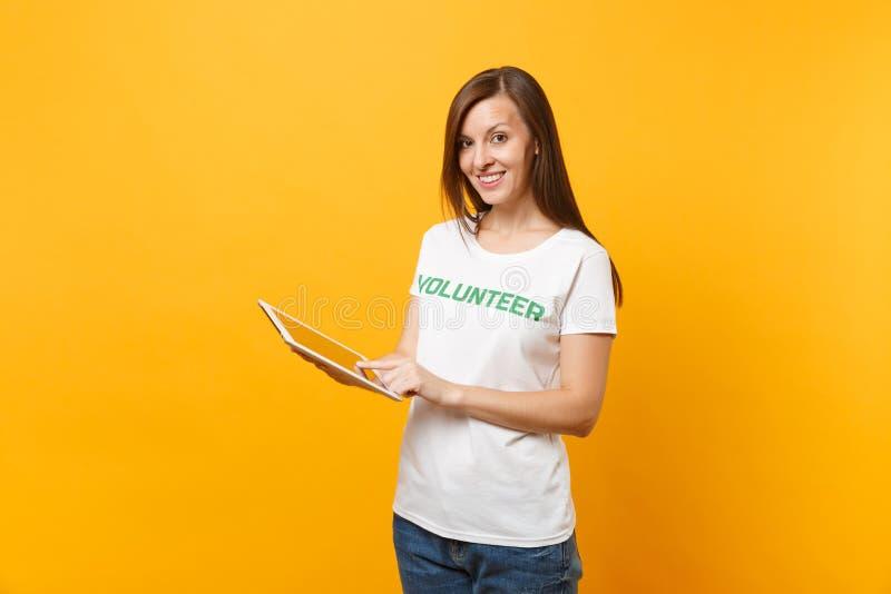 Portrait de femme dans le T-shirt blanc avec le volontaire écrit de titre de vert d'inscription utilisant l'ordinateur de PC de c image stock