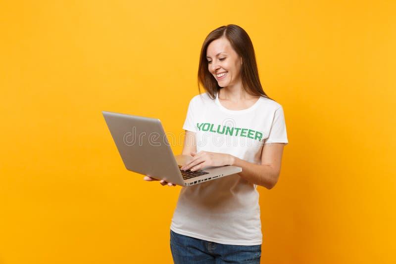 Portrait de femme dans le T-shirt blanc avec le volontaire écrit de titre de vert d'inscription utilisant l'ordinateur de PC d'or photos stock