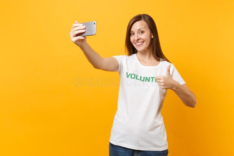 Portrait de femme dans le volontaire de titre de vert d'inscription écrit par T-shirt blanc prenant le selfie tiré au téléphone p photos stock