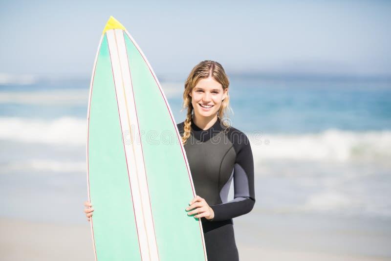 Portrait de femme dans le wetsuit tenant une planche de surf sur la plage images stock