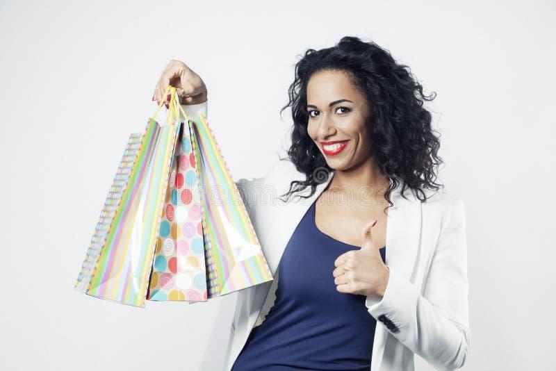 Portrait de femme de couleur heureux avec les sacs en papier parfaits d'achats, visage de sourire photos stock