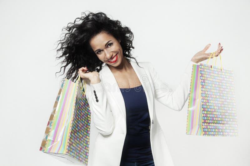 Portrait de femme de couleur heureux avec les sacs en papier parfaits d'achats, visage de sourire photographie stock