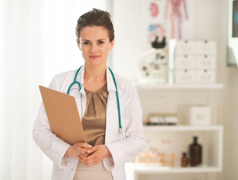 Portrait de femme de docteur avec le presse-papiers dans le bureau photographie stock