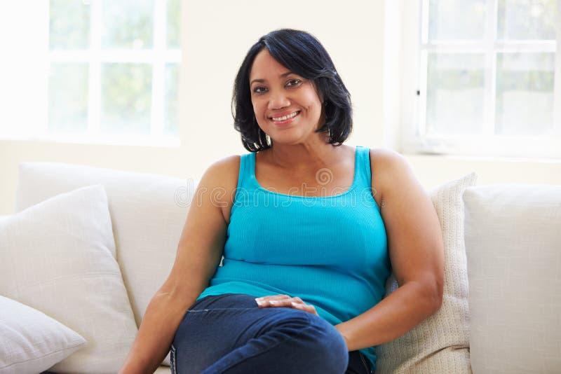 Portrait de femme de poids excessif se reposant sur le sofa photo stock
