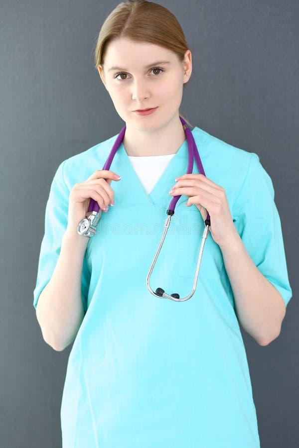 Portrait de femme de docteur avec le stéthoscope Jeune position femelle de chirurgien ou d'infirmière près de mur gris dans la cl photo libre de droits