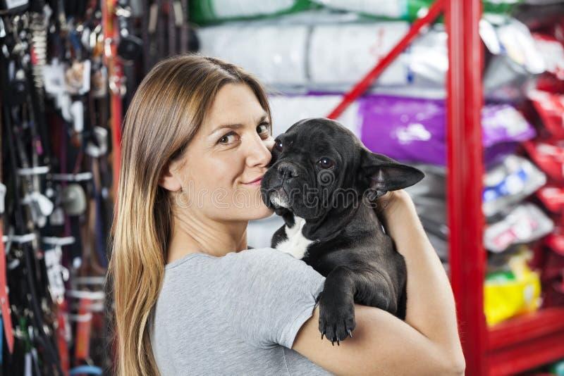 Portrait de femme embrassant le bouledogue français au magasin photographie stock libre de droits