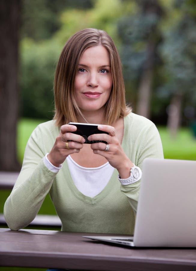 Portrait de femme en parc avec le téléphone portable images stock