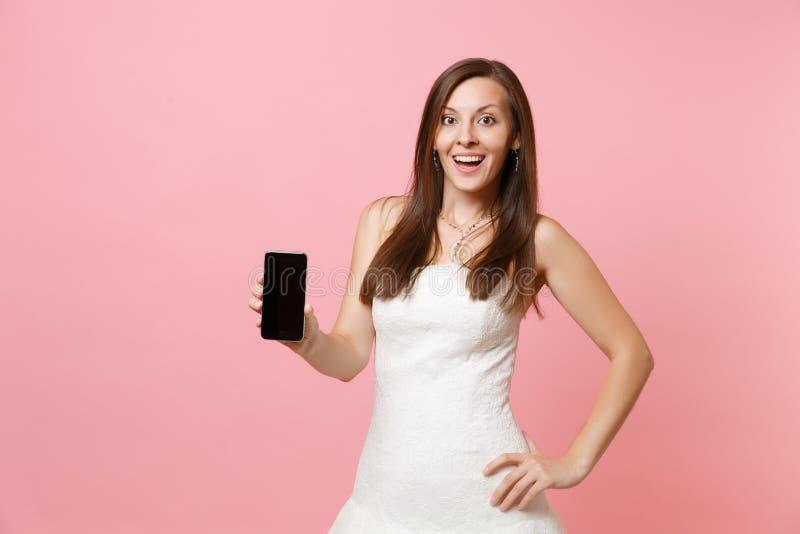 Portrait de femme enthousiaste de jeune mariée dans le téléphone portable de participation de robe de mariage avec l'écran vide n photo stock