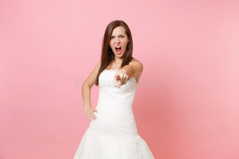 Portrait de femme fâchée stricte de jeune mariée dans l'index de pointage criard de serment blanc de robe l'épousant sur la camér photos stock
