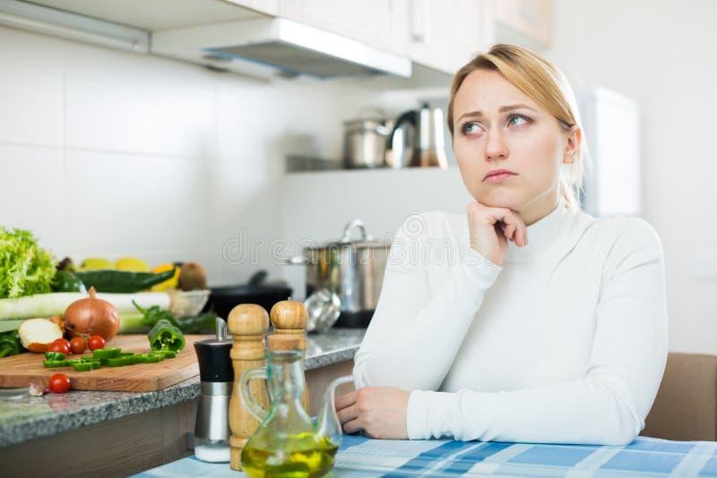 Portrait de femme fatiguée à la table de cuisine photos stock
