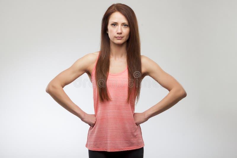 Portrait de femme de forme physique sur le fond gris Appareil-photo de regard modèle de sourire de forme physique femelle heureus photo stock
