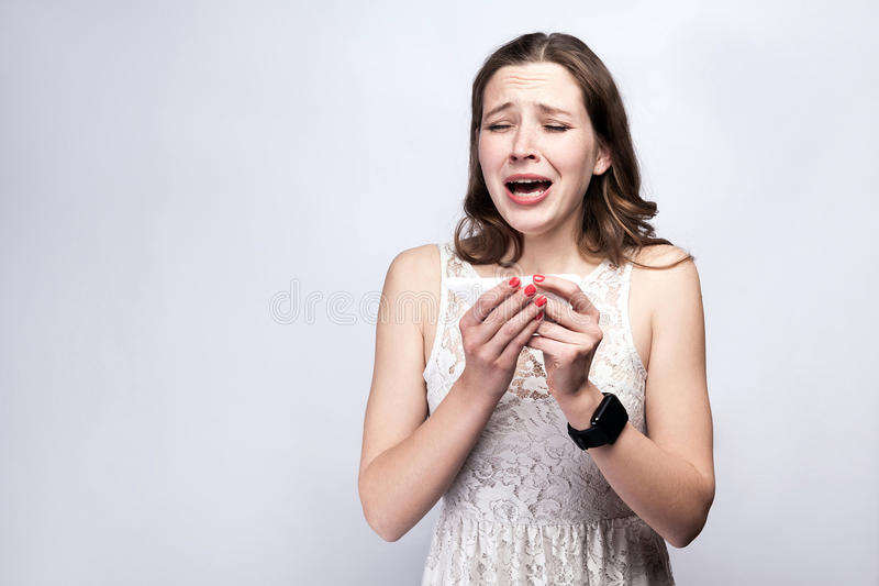 Portrait de femme froide malade avec les taches de rousseur et la robe de blanc et la montre intelligente sur le fond de gris arg images libres de droits