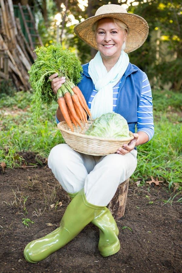 Portrait de femme heureuse avec des carottes au jardin photos stock