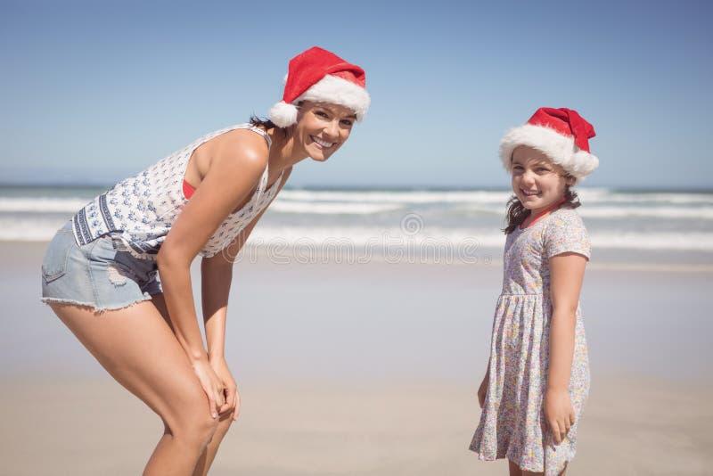 Portrait de femme heureuse avec la fille utilisant le chapeau de Santa à la plage images libres de droits