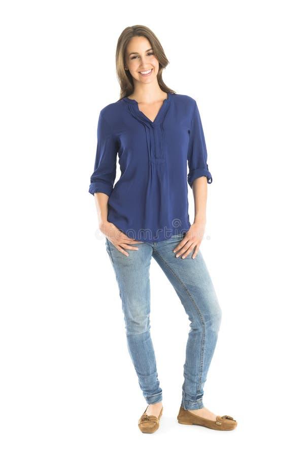 Portrait de femme heureuse se tenant avec des mains dans des poches images libres de droits