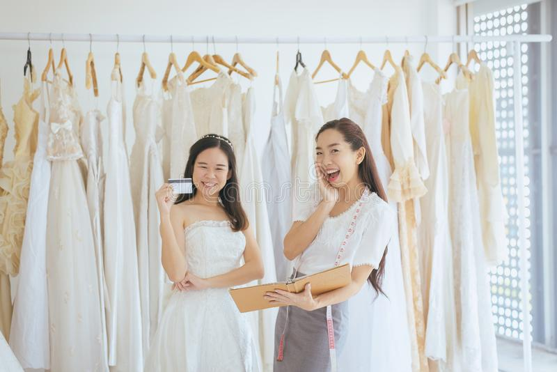 Portrait de femme heureuse tenant la carte de crédit dans le propriétaire de magasin de robe de mariage, la belle couturière réus image stock