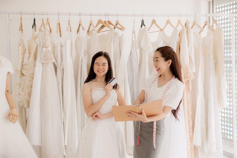 Portrait de femme heureuse tenant la carte de cr?dit dans le propri?taire de magasin de robe de mariage, la belle couturi?re r?us photographie stock