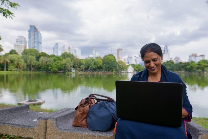 Portrait de femme indienne mûre au parc utilisant l'ordinateur portable photographie stock libre de droits