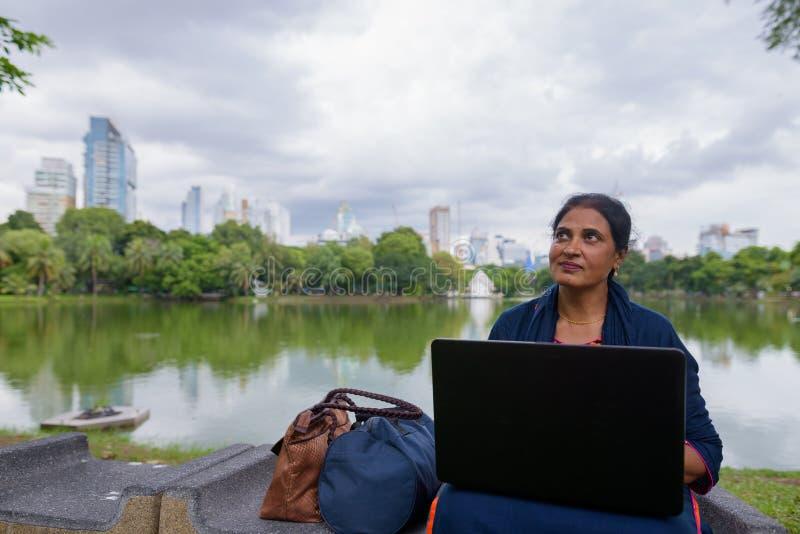Portrait de femme indienne mûre au parc utilisant l'ordinateur portable photo stock