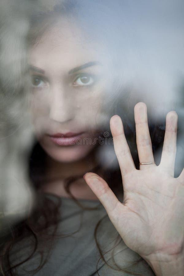 Portrait de femme mélancolique derrière la fenêtre photos stock