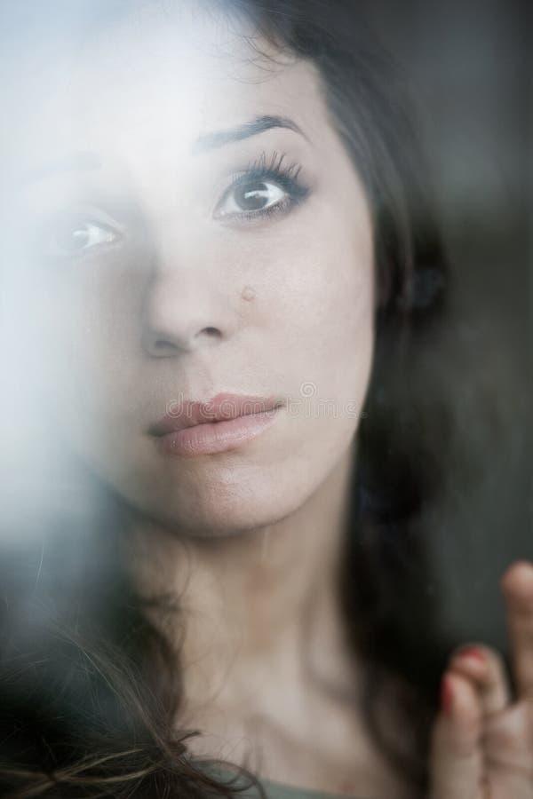 Portrait de femme mélancolique derrière la fenêtre photo libre de droits