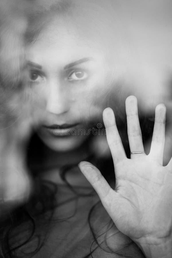 Portrait de femme mélancolique derrière la fenêtre image libre de droits